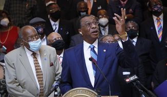 Rep. Ed Blackmon, D-Canton, points to a Mississippi state flag on an upper floor of the Capitol and calls for it to be brought down and replaced, Thursday, June 25, 2020, during a news conference with a large number of Black pastors at the Capitol in Jackson, Miss. The current flag has in the canton portion of the banner the design of the Civil War-era Confederate battle flag, that has been the center of a long-simmering debate about its removal or replacement. (AP Photo/Rogelio V. Solis)