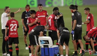 Mallorca's head coach Vicente Moreno, left, talks with his players during the Spanish La Liga soccer match between Real Madrid and Mallorca at Alfredo di Stefano stadium in Madrid, Spain, Wednesday, June 24, 2020. (AP Photo/Bernat Armangue)