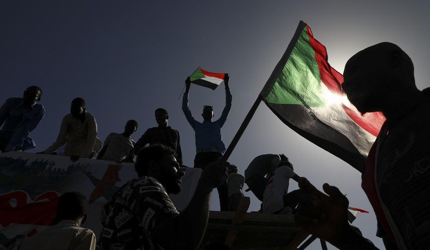 FILE - In this Nov. 19, 2019 file photo, people gather as they celebrate first anniversary of mass protests that led to the ouster of former president and longtime autocrat Omar al-Bashir. in Khartoum, Sudan. On Thursday, June 25, 2020, the United States, Germany and France have pledged hundreds of millions in aid to Sudan. The funds are intended to help the struggling African nation a year after pro-democracy protesters forced the removal of its long-time autocratic ruler, Omar al-Bashir.(AP Photo, File)