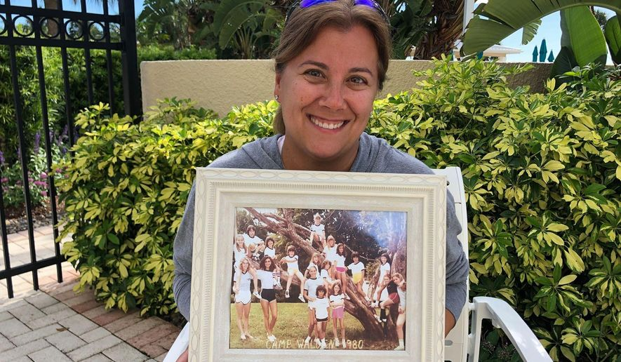 In this June 22, 2020, photo provided by Shaye Spector, Camp Walden Director Robyn Spector holds a group photo from one of her first summers at camp. Spector, 48, would have been spending her 40th summer at Camp Walden, a co-ed sleepaway camp near Lake George in Diamond Point, N.Y. (Shaye Spector via AP)
