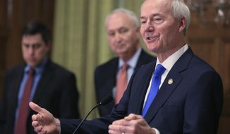 FILE - In this March 23, 2020 file photo, Gov. Asa Hutchinson, right, speaks in Little Rock Ark. Hutchinson says he's not ready to further ease restrictions on businesses as the number of coronavirus cases in the state continue to spike. Hutchinson on Thursday, June 25, 2020, said Arkansas' plans to further lift restrictions remains on pause after neighboring Texas halted its aggressive reopening of businesses. (Staton Breidenthal/The Arkansas Democrat-Gazette via AP File)
