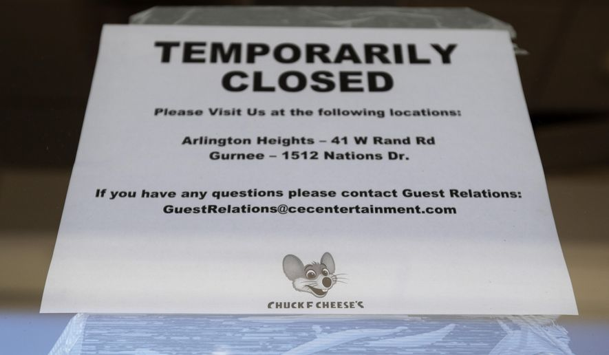 A temporarily closed sign at Chuck E. Cheese store in Vernon Hills, Ill., Thursday, June 25, 2020. Chuck E. Cheese's parent company, CEC Entertainment, filed for bankruptcy Thursday, blaming the financial strain caused by COVID-19 and the prolonged closures of its entertainment centers from stay-at-home orders issued across the United States. (AP Photo/Nam Y. Huh)