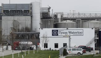 In this May 1, 2020, file photo, vehicles sit outside the Tyson Foods plant in Waterloo, Iowa. Civil rights attorney Tom Frerichs on Thursday June 25, 2020, filed a lawsuit on behalf of the estates of three Tyson Foods workers at its pork processing plant in Waterloo who died after contracting coronavirus. The lawsuit alleges the company knowingly put employees at risk during an outbreak and lied to keep them on the job. (AP Photo/Charlie Neibergall)