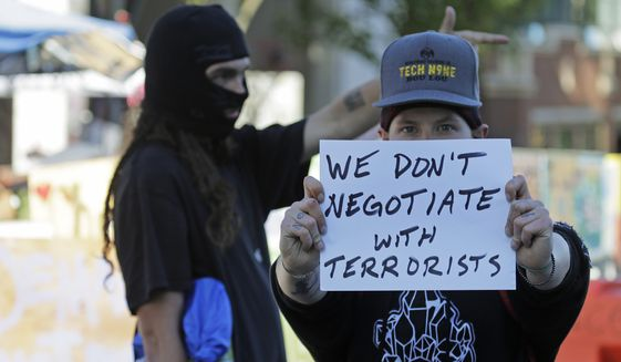 """A protester holds a sign that reads """"We don't negotiate with terrorists,"""" Friday, June 26, 2020 inside the the CHOP (Capitol Hill Occupied Protest) zone in Seattle after workers and trucks from the Seattle Department of Transportation arrived with the intention of removing barricades that had been set up in the area which has been occupied by protesters since Seattle Police pulled back from their East Precinct building following violent clashes with demonstrators earlier in the month. (AP Photo/Ted S. Warren)"""