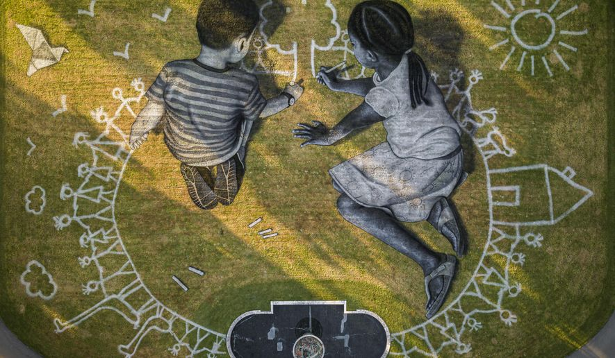 "In this picture made available Friday, June 26, 2020 an aerial view shows a giant ephemeral landart painting by Swiss French artist Saype entitled ""World in Progress"" representing two children drawing their ideal world, at the European headquarters of the United Nations in Geneva, Switzerland, Wednesday, June 24, 2020. The artwork covering 6000 square meters was produced with biodegradable paints made from natural pigments such as coal and chalk. The fresco, offered by Switzerland, for the the 75th anniversary of the signing of the United Nations Charter in San Francisco on 26.6.1945 will be inaugurated by Swiss Federal Councillor Ignazio Cassis, in the presence of the Director-General of the United Nations Office in Geneva, Tatiana Valovaya. (Valentin Flauraud/Keystone via AP)"
