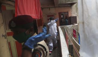 A health worker urges residents to attend a free medical checkup camp at Dharavi, one of Asia's biggest slums, in Mumbai, India, Friday, June 26, 2020. India is the fourth hardest-hit country by the pandemic in the world after the U.S., Russia and Brazil. (AP Photo/Rafiq Maqbool)