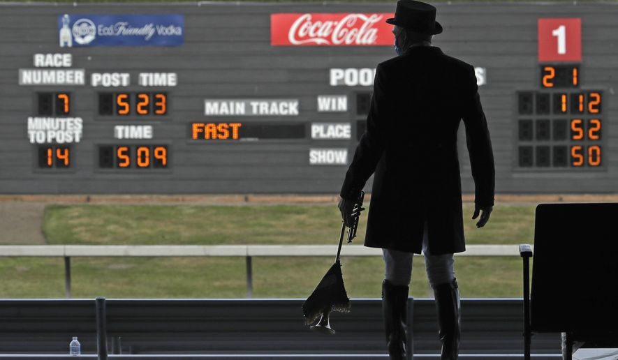 Track bugler Dan Harrington stands near empty seats Wednesday, June 24, 2020, before playing just before a race at Emerald Downs Racetrack in Auburn, Wash., on the first day of thoroughbred horse racing at the track since all professional sports in Washington state were curtailed in March by the outbreak of the coronavirus. No spectators were allowed, but online wagering was available and the races were streamed. Organizers hope to continue racing into October on a modified schedule. (AP Photo/Ted S. Warren)