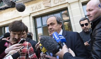FILE - In this Friday, April 29, 2016 file photo, UEFA President Michel Platini leaves the international Court of Arbitration for Sport, CAS, surrounded by media after a hearing in Lausanne, Switzerland. Former UEFA president Michel Platini is formally under investigation in Switzerland for a $2 million payment he got from FIFA in 2011. (Laurent Gillieron/Keystone via AP, File)