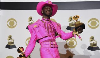 "In this Jan. 26, 2020, photo, Lil Nas X poses in the press room with the awards for best music video and best pop duo/group performance for ""Old Town Road,"" at the 62nd annual Grammy Awards in Los Angeles. (AP Photo/Chris Pizzello) **FILE**"