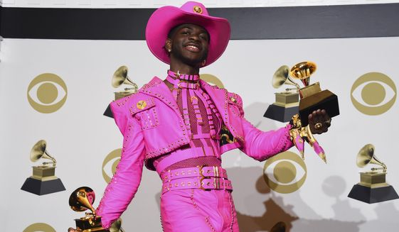 """In this Jan. 26, 2020, photo, Lil Nas X poses in the press room with the awards for best music video and best pop duo/group performance for """"Old Town Road,"""" at the 62nd annual Grammy Awards in Los Angeles. (AP Photo/Chris Pizzello) **FILE**"""