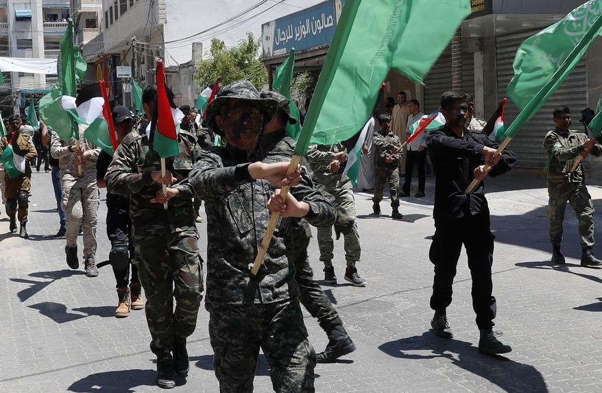 Hamas supporters paint heir faces while mach with their green and national flags during a protest against Israel's plan to annex parts of the West Bank and  U.S. President Donald Trump's mideast initiative, after Friday prayer at the main road of Khan Younis City, Gaza Strip, Friday, June 26, 2020. (AP Photo/Adel Hana)