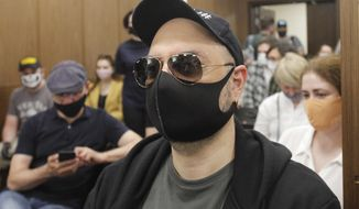 Russian film and theater director Kirill Serebrennikov wearing a protective face mask sits prior to his court hearing at the Meshchansky court in Moscow, Russia, Friday, June 26, 2020. A court in Moscow is expected to deliver a verdict on Friday to the acclaimed theater director accused of embezzling state funds, in a case widely seen as politically motivated. (AP Photo)