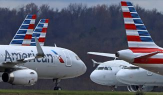 In this March 31, 2020, file photo, American Airlines planes are parked at Pittsburgh International Airport in Imperial, Pa.  There will be no more attempts at social distancing on American Airlines flights. The airline said Friday, June 26,  that it will start booking flights to full capacity next week. (AP Photo/Gene J. Puskar, file) ** FILE **