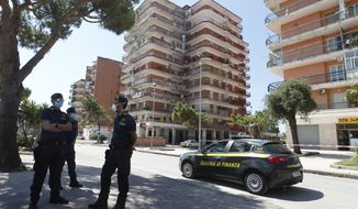 Police officers stand at a road block in front of a big apartment complex where dozens of COVID-19 cases have been registered among a community of Bulgarian farm workers, in Mondragone, in the southern Italian region of Campania, Friday, June 26, 2020. The governor of the region is insisting that the farm workers should stay inside for 15 days, not even emerging for food, and that the national civil protection agency should deliver them groceries. (AP Photo/Riccardo De Luca)