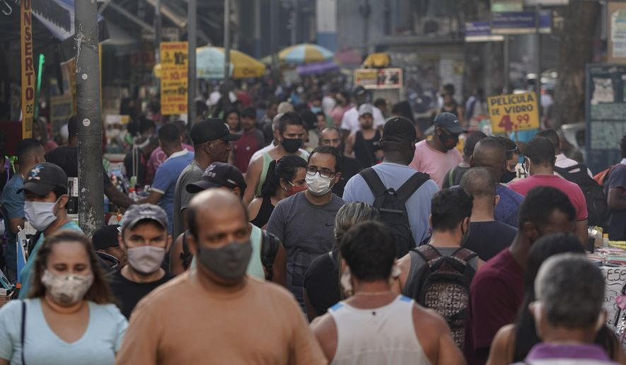 Pedestrians, some wearing protective face masks, walk through a street market in downtown Rio de Janeiro, Brazil, Thursday, June 25, 2020. With Latin America now the epicenter of the new coronavirus pandemic, but with hundreds of millions relying on these markets for food and livelihoods, the debate now centers on whether and how they can ever operate safely. (AP Photo/Leo Correa)