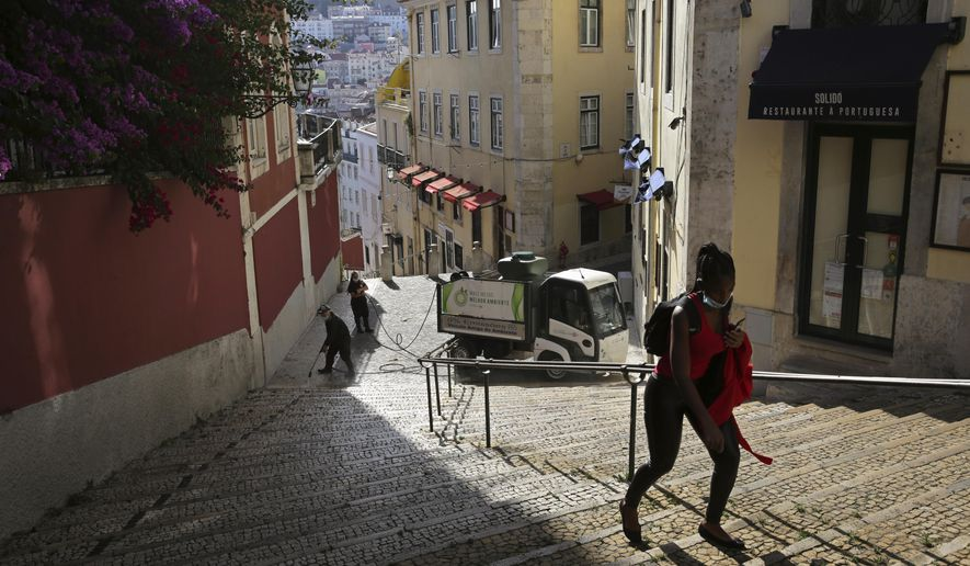 In this photo taken Wednesday, June 24, 2020, a woman wearing a face mask walks past workers washing the street in Lisbon's old center. Portugal avoided the dramatic numbers of infections and deaths recorded by some other European Union countries during the early months of the coronavirus outbreak but since ending its state of emergency and lockdown at the end of April, its total of officially recorded new infections has remained stubbornly high. (AP Photo/Armando Franca)