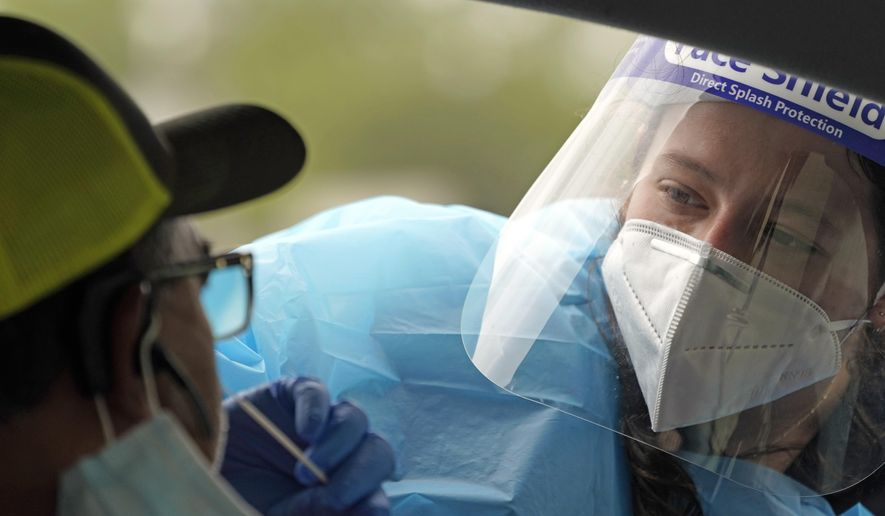"""Healthcare professional Kenzie Anderson takes a sample from a patient at a United Memorial Medical Center COVID-19 testing site Friday, June 26, 2020, in Houston. The number of COVID-19 cases continues to rise across the state. Texas Gov. Greg Abbott has said that the state is facing a """"massive outbreak"""" in the coronavirus pandemic and that some new local restrictions may be needed to protect hospital space for new patients. (AP Photo/David J. Phillip)"""
