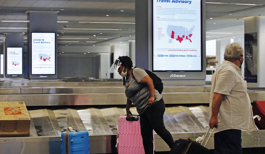 """An arriving passenger wearing a face shield, left, collects her luggage in the baggage claim area of LaGuardia Airport's Terminal B, Thursday, June 25, 2020, in New York. New York, Connecticut and New Jersey are asking visitors from states with high coronavirus infection rates to quarantine for 14 days. The """"travel advisory"""" affects three adjacent Northeastern states that managed to check the spread of the virus this spring as New York City became a hot spot. Travelers from mostly southern and southwestern states including Florida, Texas Arizona and Utah will be affected starting Thursday. The two-week quarantine will last two weeks from the time of last contact within the identified state. (AP Photo/Kathy Willens)"""