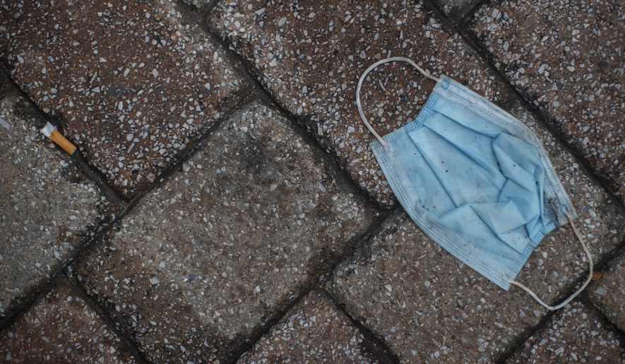 In this June 18, 2020, file photo a discarded face mask and cigarette butt litter the sidewalk outside the Eastern Market in Washington. On Friday, June 26, Vice President Mike Pence said Americans should look to their state and local leadership for modeling their behavior during the coronavirus pandemic. The comments only days after President Donald Trump held two campaign events that drew hundreds of participants but few wearing masks. (AP Photo/Carolyn Kaster, File)