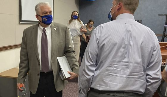 FILE - In this Wednesday, June 24, 2020, file photo, Nevada Gov. Steve Sisolak exits a news conference at the Nevada State Legislature in Carson City, Nev. Sisolak announced Nevada would join California, Washington and North Carolina in requiring individuals wear masks in public places to contain the spread of the coronavirus. (AP Photo/Samuel Metz, File)