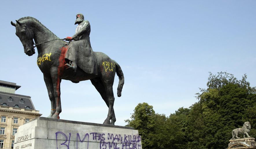 In this Wednesday, June 10, 2020, file photo, a statue of Belgium's King Leopold II is smeared with red paint and graffiti in Brussels. With the protests sweeping the world in the wake of the killing of George Floyd in Minneapolis, King Leopold II is now increasingly seen as a stain on the nation. (AP Photo/Virginia Mayo, File)