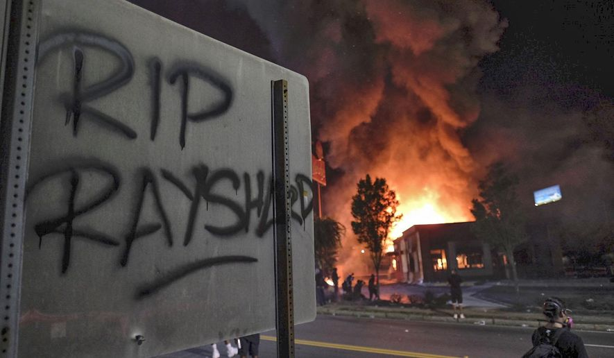 A Wendy's restaurant, background, burns Saturday, June 13, 2020, in Atlanta after demonstrators set it on fire. Demonstrators were protesting the death of Rayshard Brooks, a black man who was shot and killed by Atlanta police Friday evening following a struggle in the Wendy's drive-thru line. (Ben GrayAtlanta Journal-Constitution via AP)