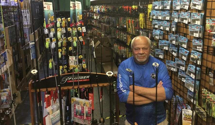 In this Wednesday, June 17, 2020 photo, Dave Becker, a sales associate at Blue Ribbon Bait & Tackle in Oakdale, Minn., poses behind a fishing rod display. Amid the coronavirus outbreak, the store has been nearly selling out its entry-level fishing rods and reels regularly each week before a fresh supply arrives. Fishing activity has skyrocketed during the pandemic. (Dave Orrick/Pioneer Press via AP)