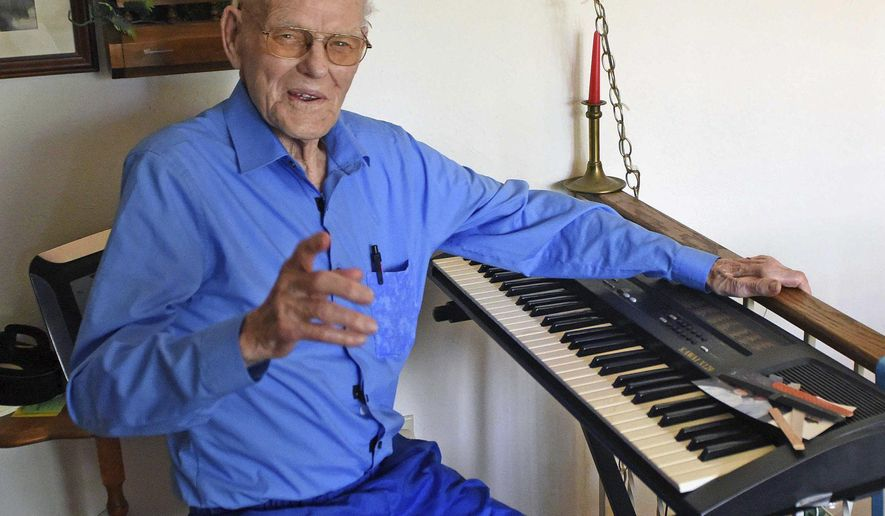 "Music has been a big part of life for Wilton, North Dakota native Orville Speten, 100, pictured in a June 17, 2020 photo. Speten still plays organ and sings from memory a repertoire of songs from years ago. Speten, who was born on a rural Wilton farm, is known for saying ""use it or lose it."" (Tom Stromme/The Bismarck Tribune via AP)"