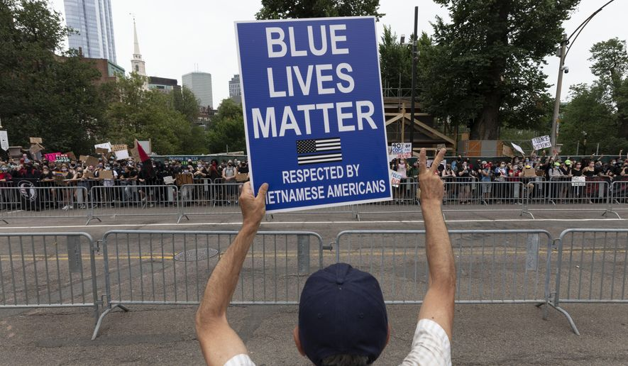 A demonstrator from a small group holding what it called a pro-police rally faces several hundred counterprotesters outside the Statehouse, Saturday, June 27, 2020, in Boston. (AP Photo/Michael Dwyer) ** FILE **