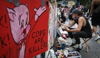 A protester paints signs that cover a subway station entrance at an encampment outside City Hall, Friday, June 26, 2020, in New York. (AP Photo/John Minchillo)