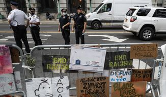 Police stand on the street beside a protest encampment surrounded by handmade signs and barricades outside City Hall, Friday, June 26, 2020, in New York. (AP Photo/John Minchillo)