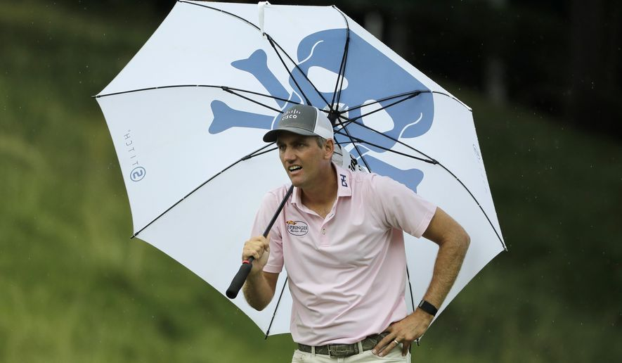 Brendon Todd looks at a competitors tee shot while sheltering from the rain with an umbrella on the 18th hole during the third round of the Travelers Championship golf tournament at TPC River Highlands, Saturday, June 27, 2020, in Cromwell, Conn. (AP Photo/Frank Franklin II)