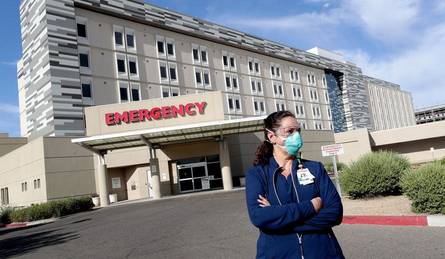 Caroline Maloney stands outside HonorHealth's Scottsdale Osborn Medical Center at the end of her overnight shift early Friday, June 26, 2020 in Scottsdale, Ariz. Arizona nurses and doctors find themselves on the frontline as the coronavirus rips through the state, making it one of the world's hot spots.  (AP Photo/Matt York)