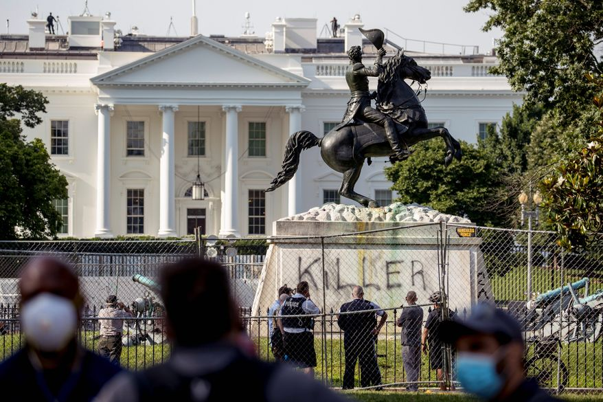 Four men have been charged with damaging and trying to tear down the Andrew Jackson statue in Lafayette Park, which is adjacent to the White House. Prosecutors said all four men were caught on video using straps to try to pull down the statue. (Associated Press) ** FILE **