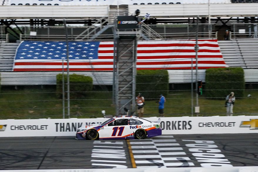 Denny Hamlin gets the checkered flag as he crosses the finish line to win the NASCAR Cup Series auto race at Pocono Raceway, Sunday, June 28, 2020, in Long Pond, Pa. (AP Photo/Matt Slocum)