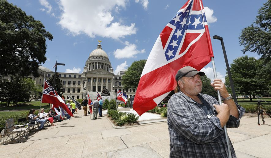 """I love this flag,"" states David Flynt of Hattiesburg, while standing outside the state Capitol with other current Mississippi flag supporters in Jackson, Miss., Sunday, June 28, 2020. Lawmakers in both chambers are expected to debate state flag change legislation today. Mississippi Governor Tate Reeves has already said he would sign whatever flag bill the Legislature decides on. (AP Photo/Rogelio V. Solis)"