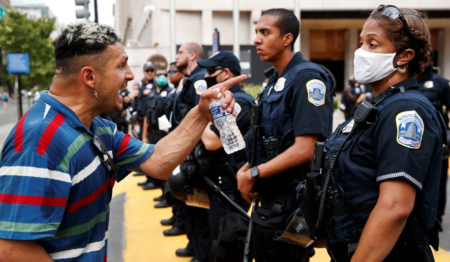 A man yells at a Metropolitan Police officer as demonstrators protest in front of a police line on the section of 16th Street renamed Black Lives Matter Plaza, Tuesday, June 23, 2020, in Washington, over the death of George Floyd, a black man who was in police custody in Minneapolis. Floyd died after being restrained by Minneapolis police officers. (AP Photo/Jacquelyn Martin)