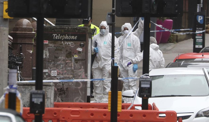 Police and forensic officers at the scene where a man was shot by armed officers after another police officer was injured during an attack on Friday, in Glasgow, Scotland, Sunday June 28, 2020. (Andrew Milligan/PA via AP)