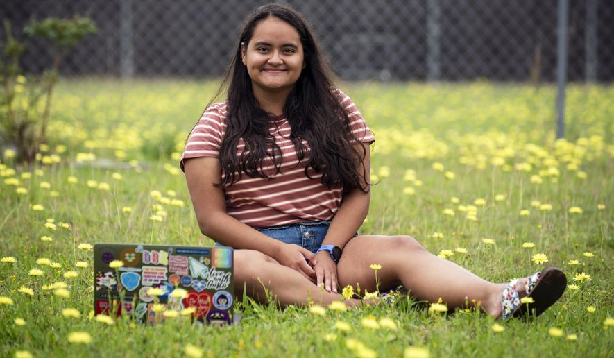 """In this May 21, 2020, photo, Ileana Valdez, 20, an undergrad student at Yale, poses for a photo outside of her home in Red Oak, Texas. Valdez created an online dating site for college students called OKZoomer. """"I started OKZoomer because I wanted to help students connect without the interference of superficial biases that modern dating apps promote,"""" said Valdez. (Ben Torres/The Dallas Morning News via AP)"""