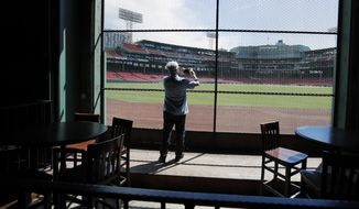 In this June 25, 2020, photo, a reporter photographs the view of the baseball field at Fenway Park from the Bleacher Bar in Boston. Tucked under the center field seats at Fenway Park, down some stairs from Lansdowne Street in an area previously used as the visiting team's batting cage, is a sports bar that is preparing to reopen from the coronavirus shutdown. If Major League Baseball's plans remain on schedule, it may be one of the few places fans will be able to watch a game in person this season. (AP Photo/Elise Amendola) ** FILE **