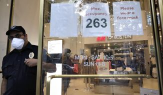 A signs at the entrance to a clothing store requests that customers wear a mask out of concern for the coronavirus, Sunday, June 28, 2020, in Boston. Under step two in phase two of the state's plan to reopen the economy during the coronavirus pandemic, beginning June 22, 2020 clothing stores are allowed to offer the use of dressing rooms, by appointment only. (AP Photo/Steven Senne)