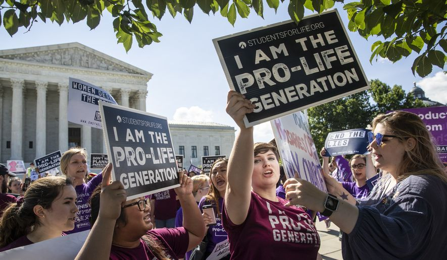 Pro-life and anti-abortion advocates demonstrate in front of the Supreme Court early Monday, June 25, 2018. The justices are expected to hand down decisions today as the court's term comes to a close. (AP Photo/J. Scott Applewhite)