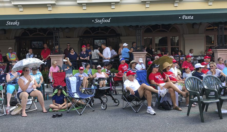 """In this Oct. 3, 2019 file photo, supporters of President Donald Trump wait outside in a town square in The Villages, Fla., before an appearance by the president. There has always been a low-boil tension in The Villages between the Republican majority and the much smaller cohort of Democrats, but a veneer of good manners in Florida's Friendliest Hometown"""" mostly prevailed on golf courses and at bridge tables. Those tensions got international attention last weekend when President Donald Trump tweeted approvingly of a video showing one of his supporters at the retirement community chanting a racist slogan associated with white supremacists.  (AP Photo/Mike Schneider, File)"""