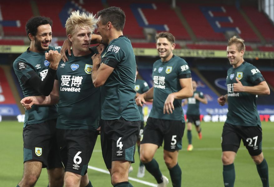Burnley's Ben Mee, second left, is congratulated by teammates after scoring his team's first goal during the English Premier League soccer match between Crystal Palace and Burnley at Selhurst Park, in London, England, Monday, June 29, 2020. (AP Photo/Catherine Ivill,Pool)