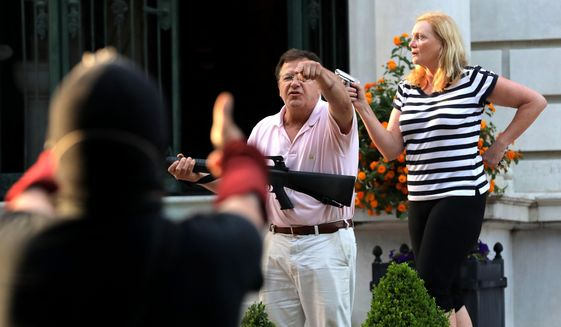Armed homeowners standing in front their house along Portland Place confront protesters marching to St. Louis Mayor Lyda Krewson's house Sunday, June 28, 2020, in the Central West End of St. Louis. The protesters called for Krewson's resignation for releasing the names and addresses of residents who suggested defunding the police department. (Laurie Skrivan/St. Louis Post-Dispatch via AP)
