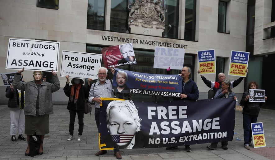 Supporters of WikiLeaks founder Julian Assange protest in front of Westminster Magistrates' Court in London, Monday, June 29, 2020, where he is expected to appear in custody for the extradition case management hearing. Assange was arrested last year after being evicted from the Ecuadorian Embassy in London, where he had sought refuge to avoid being sent to Sweden over allegations of rape and sexual assault, and is at the center of an extradition tussle over whether he should be sent to the United States. (AP Photo/Frank Augstein)