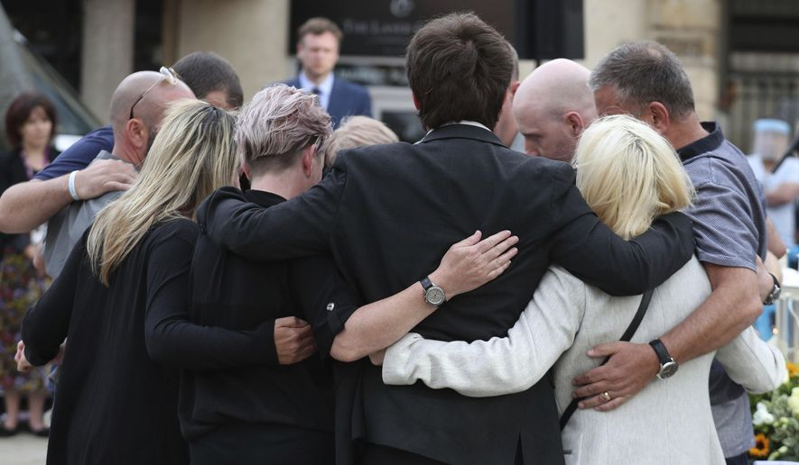 Family members of the three victims comfort each other after lighting candles during a vigil in the town of Reading, England, in memory of three people who were killed in the Reading terror attack in Forbury Gardens in the town centre. Three people were stabbed to death by a lone attacker on Saturday June 27, in what is being treated as a terror attack.  (Steve Parsons/PA via AP)