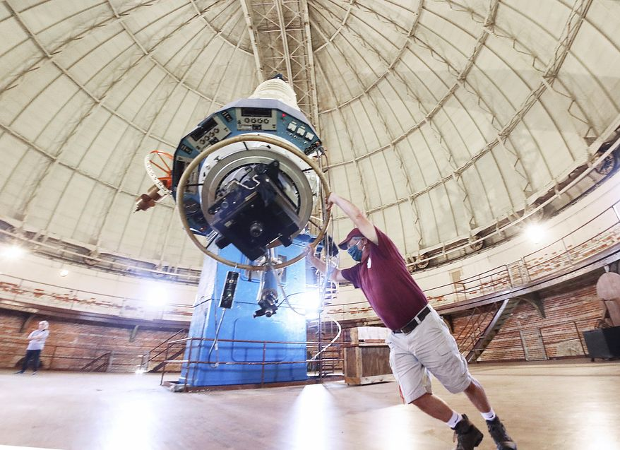 Built in the 1890's the world's largest refracting telescope is maneuvered Wednesday, June 10, 2020, by hand by Ed Struble, who has served for 30 years as director of building and grounds at the Yerkes Observatory in Williams Bay, Wis. Recently, the University of Chicago transferred ownership of the 123-year-old facility to the Yerkes Future Foundation, a preservation group that plans to restore, refurbish and reopen the research center. (John Hart/Wisconsin State Journal via AP)