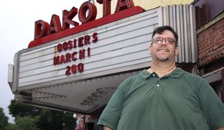 In this June 18, 2020 photo, Lewis and Clark Theatre Company (LCTC) President Michael Schumacher stands in front of the Dakota Theater marquee in downtown Yankton, S.D. Even during a pandemic, Lewis and Clark Theatre Company (LCTC) members believe the show must go on. The stage has remained dark since mid-March, when the first COVID-19 cases were detected in Yankton and the theater was shut down. (Kelly Hertz/Yankton Press & Dakotan via AP)