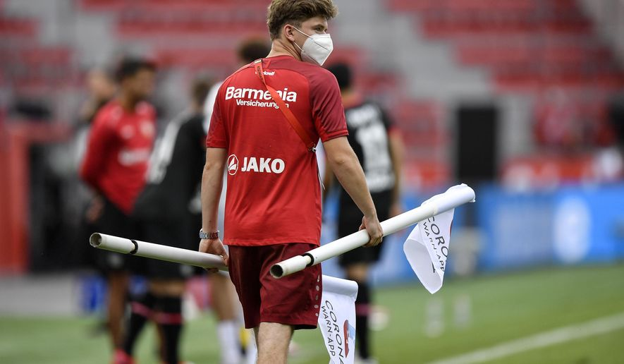A ball boy carries the corner flags with a corona app commercial on it after the German Bundesliga soccer match between Bayer 04 Leverkusen and FSV Mainz 05 in Leverkusen, Germany, Saturday, June 27, 2020. Because of the coronavirus outbreak all soccer matches of the German Bundesliga take place without spectators. (AP Photo/Martin Meissner, Pool)